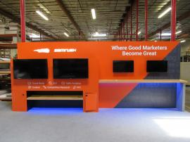 Custom Inline Exhibit with (4) Monitor Mounts, Backlit Logo, Locking Storage, and Shelves